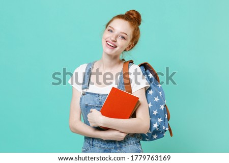 Pretty young readhead student girl in casual denim clothes with backpack posing isolated on blue turquoise background studio portrait. Education in high school university college concept. Hold books Foto stock ©