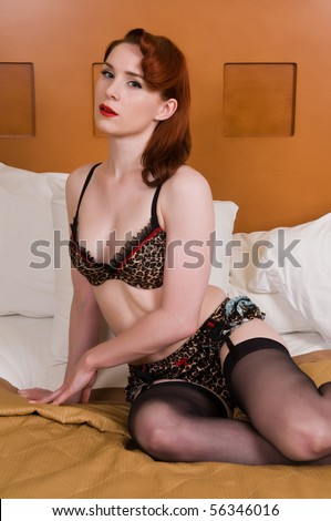 Pretty young redhead dressed in leopard print lingerie