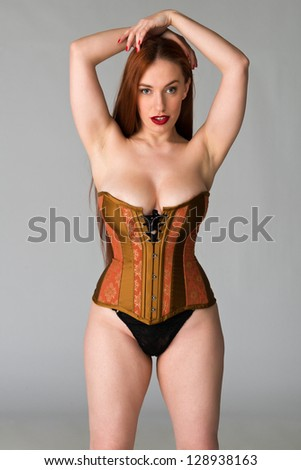 Pretty young redhead in a copper and brass corset - stock photo