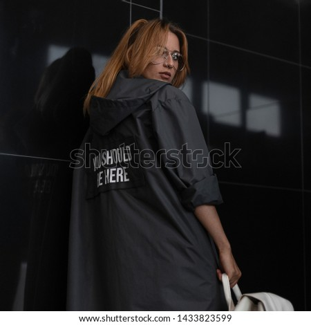Pretty young redhead woman hipster in a fashionable raincoat with hood in stylish glasses with a stylish vintage backpack is standing near a black wall in a room. American urban girl fashion model.