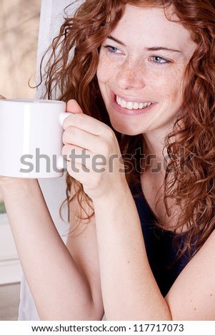 pretty young redhead woman with freckles and coffe smile and laugh