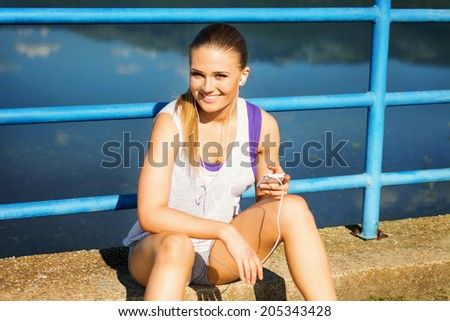 Pretty young runner woman with smart phone and headphones sitting by the lake on the bridge. Teenage fit blonde Caucasian girl in sportswear making a running playlist. #205343428