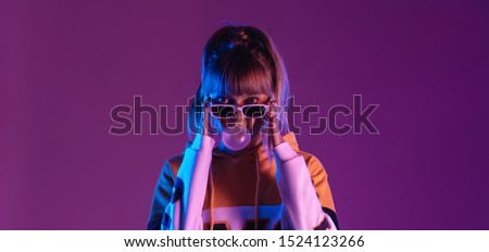 Pretty young 20s fashion teen girl model wear glasses blowing bubble gum looking at camera standing at purple studio background, igen teenager in trendy stylish night glow 80s 90s concept, portrait