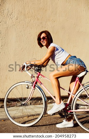 Pretty young sexy hot sport style woman posing in summer hot weather on the street riding vintage bicycle and have fun alone