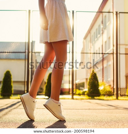 Pretty young sexy sport style woman standing alone in summer evening on the street in sunshine bright light and having fun outdoor