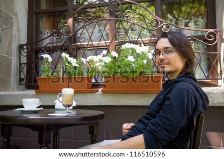 Pretty young sitting in sidewalk terrace cafe - stock photo
