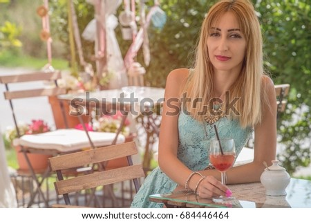 Pretty young slim girl at a vintage garden pub at summer