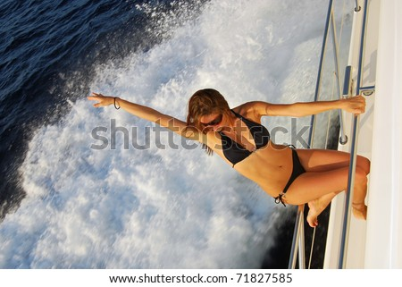 Pretty young slim sexy brunette woman in sunglasses and black stylish bikini on private speed-boat yacht on vacation in summer time smiling and touch her hair, sailing in Mediterranean sea