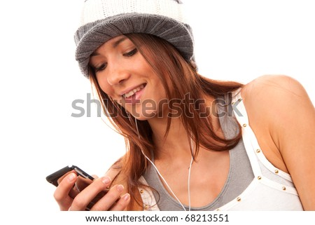 Pretty young teenage girl typing and reading text message on her new modern cell phone mobile and listening music in headphones isolated on a white background