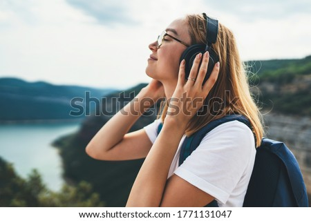 pretty young tourist woman with backpack and  hipster glasses closes her eyes listens favorite music with headphones enjoying freedom of  hiking background natura mountain landscape on trip outdoors Foto d'archivio ©