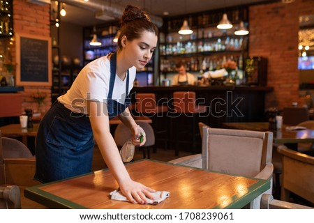 Pretty young waitress in apron bending over wooden table while using detergent and duster to clean it for new guests of restaurant
