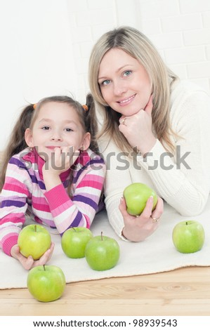 Pretty young woman and her little daughter lying on the floor with green apples