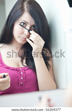 pretty young woman applying mascara /eye shadows in front of a mirror