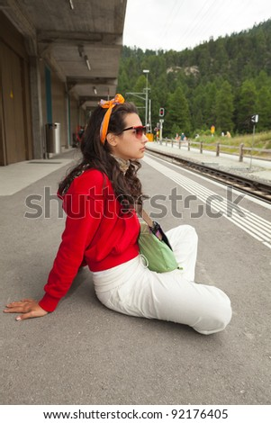 Pretty young woman at a Swiss station waiting for a train.