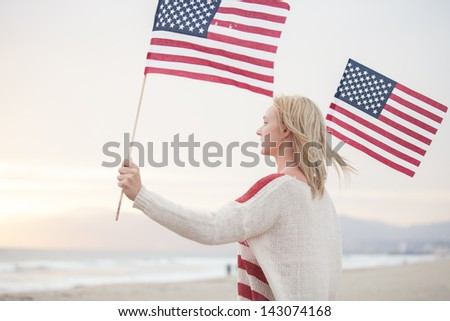 Pretty Young Woman at the Beach holding American Flags facing the ocean