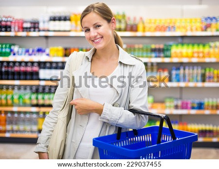 Pretty young woman buying groceries in a supermarket/mall/grocery store (color toned image; shallow DOF)