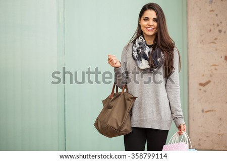 Pretty young woman carrying a purse and some shopping bags while visiting a shopping center