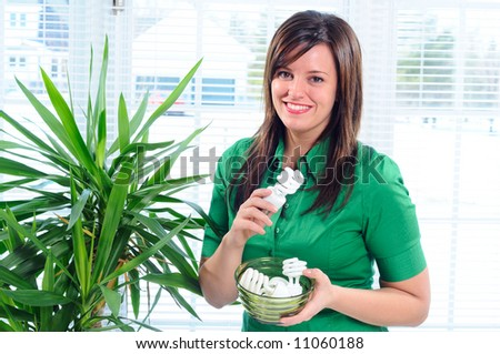 Pretty Young Woman Changing The Light Bulbs In Her Home To Low Energy Compact Fluorescent CFL