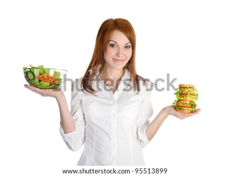 Pretty young woman choice lettuce salad or fast food. Isolated on the white background