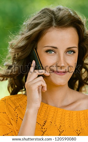 Pretty young woman close-up in orange sweater talking on cell phone, against green of summer park.