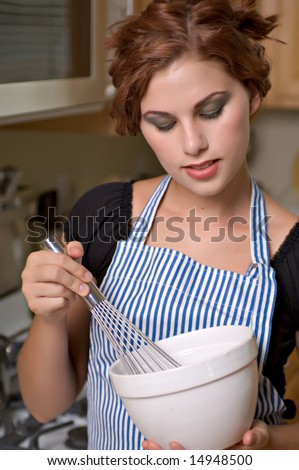 Pretty young woman cooks dinner in her kitchen