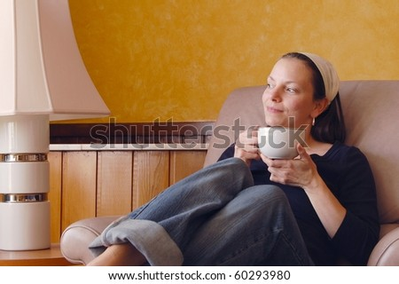 Pretty Young Woman Daydreaming on a Recliner while Sipping Coffee
