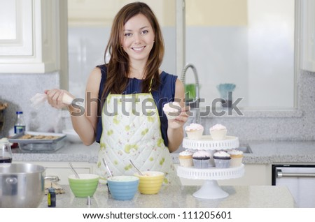 Pretty young woman decorating cupcakes