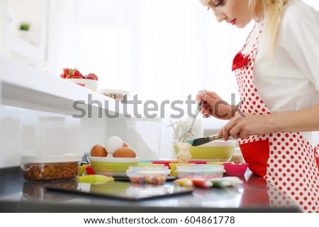 Pretty Young Woman Decorating Cupcakes On Her Kitchen. Portrait Of A  Beautiful Female Business Owner