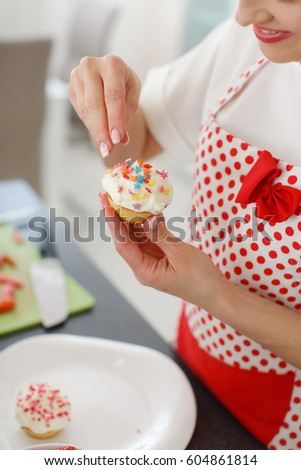 detail pretty young woman decorating cupcakes on her kitchen portrait of a beautiful female business owner