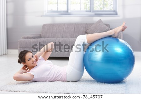 Pretty young woman doing sit-ups with fit ball, smiling.?