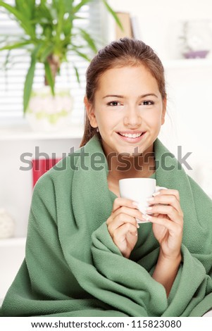 pretty young woman drinking tea  at home covered with blanket