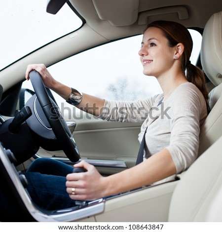 Pretty young woman driving her brand new car shallow DOF; color toned image)