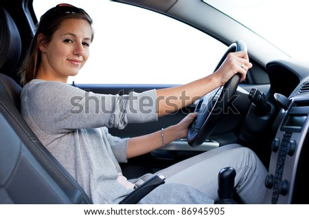 Pretty young woman driving her new car