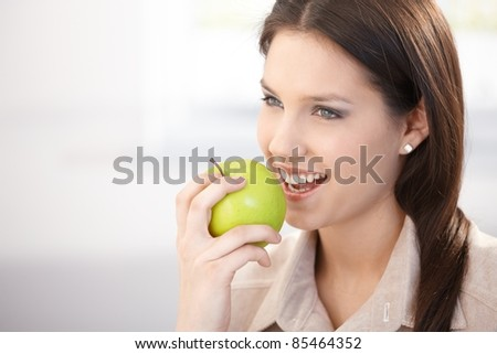 Pretty young woman eating green apple, smiling.?