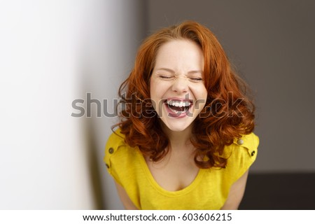 Pretty young woman enjoying a good joke having a hearty laugh with mouth open and eyes closed as she leans towards the camera