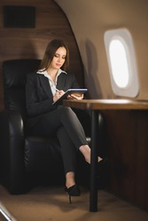 Pretty young woman entrepreneur working on tablet computer in private airplane. Full length portrait attractive businesswoman wearing black pantsuit sitting in jet and working.