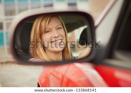 Pretty young woman face in car mirror