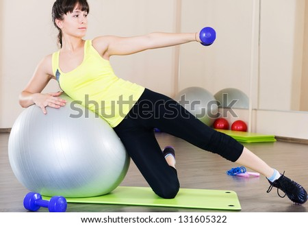 Pretty young woman fitness workout in gym with fitball