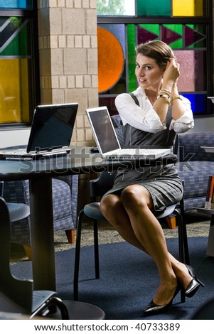 Pretty young woman fixing hair, sitting at table with laptop computers