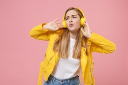 Pretty young woman girl in yellow leather jacket posing isolated on pastel pink wall background studio portrait. People emotions lifestyle concept. Mock up copy space. Listen music with headphones