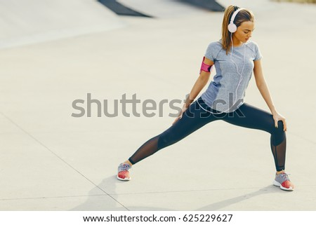 Pretty young woman having exercise outdoors