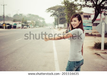 Pretty young woman hitchhiking along a road in thailand