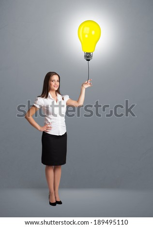 Pretty young woman holding a light bulb balloon