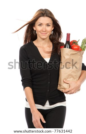 Pretty young woman holding a shopping bag full of vegetarian groceries