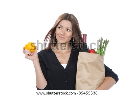 Pretty young woman holding a shopping bag full of vegetarian groceries and orange in hand on a white background