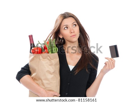 Pretty young woman holding a shopping bag full of vegetarian groceries in supermarket with tomatoes, asparagus, bottle of red wine and credit card isolated on white background