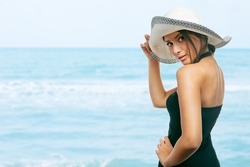 Pretty young woman holding her hat on her head, at the beach