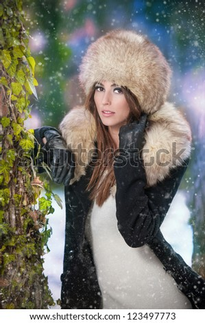 pretty young woman in a winter fashion shot.Winter wild girl on snow.Winter Girl with beautiful make up, and snow flake, forest background.Portrait of attractive woman