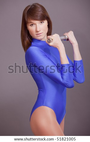 pretty young woman in blue leotard doing exercises with dumbbell