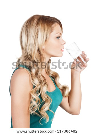 Pretty young woman in blue singlet is holding a glass of water. Beautiful blonde long-haired girl is drinking water from glass on white. Studio shot. - stock photo